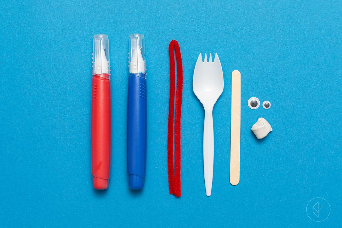 ingredients to make a Forky laid out on a blue background: red and blue pens, red pipe cleaner, spork, popsicle stick, googly eyes, and a wad of putty