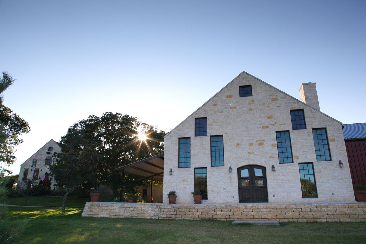 The exterior of Becker Vineyards in Texas. The building is multicolor brick and there are multiple windows. There is a lawn in the foreground.