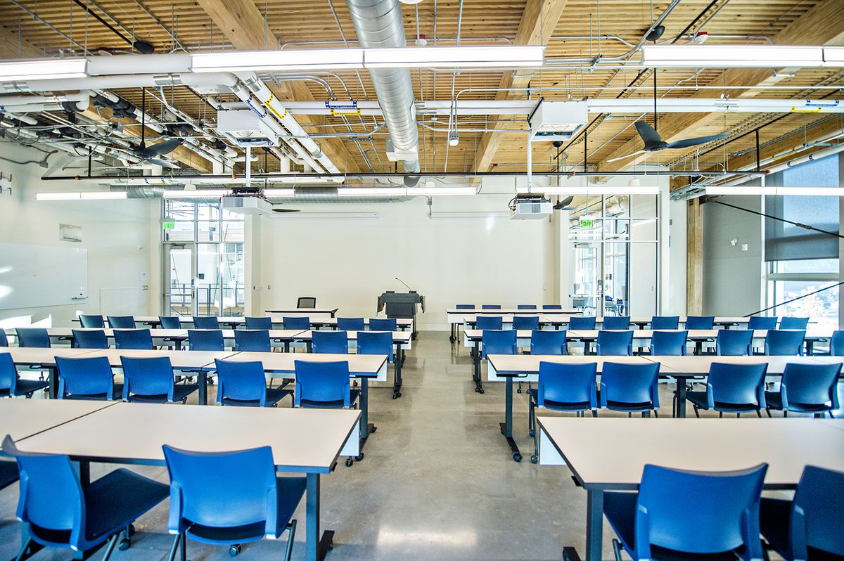 A classroom with blue chairs and white walls.