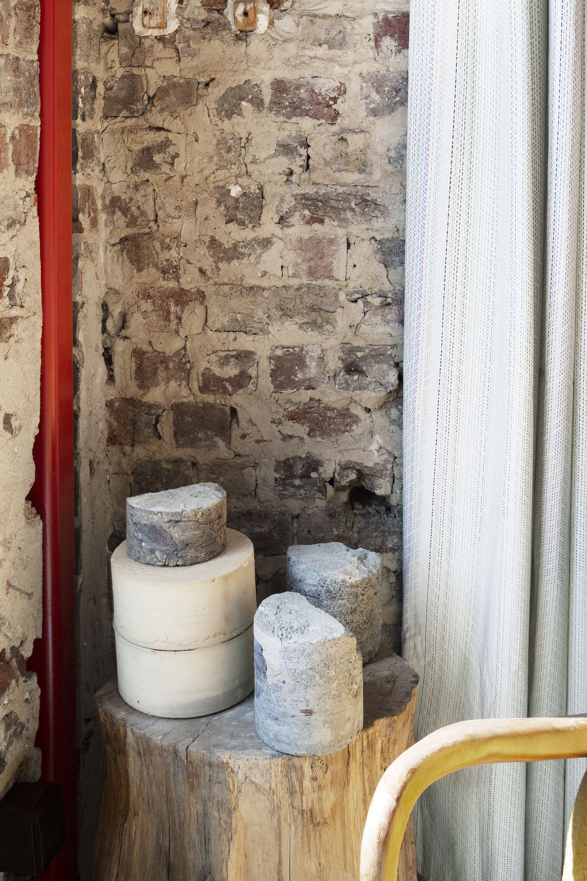 The corner of a room. The wall is exposed brick. There is a tree stump with various masonry objects on top of it. A white curtain hangs to the side.