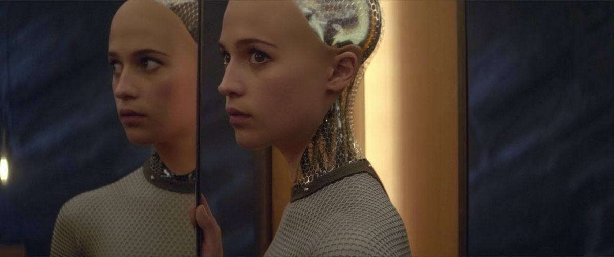 Ex Machina: Ava stands next to a mirror