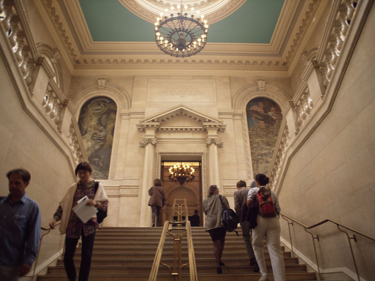 A capacious ceiling above a wide staircase, and there are people going up and down.