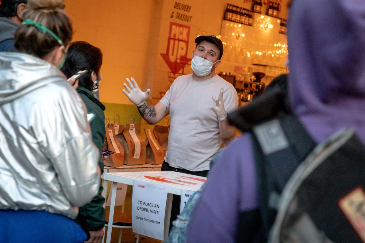 A Tacombi staffer explains the situation to waiting customers and couriers
