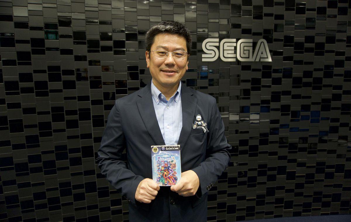 Takao Miyoshi segura uma cópia do GameCube de Phantasy Star Online em frente a uma parede com o logotipo da Sega