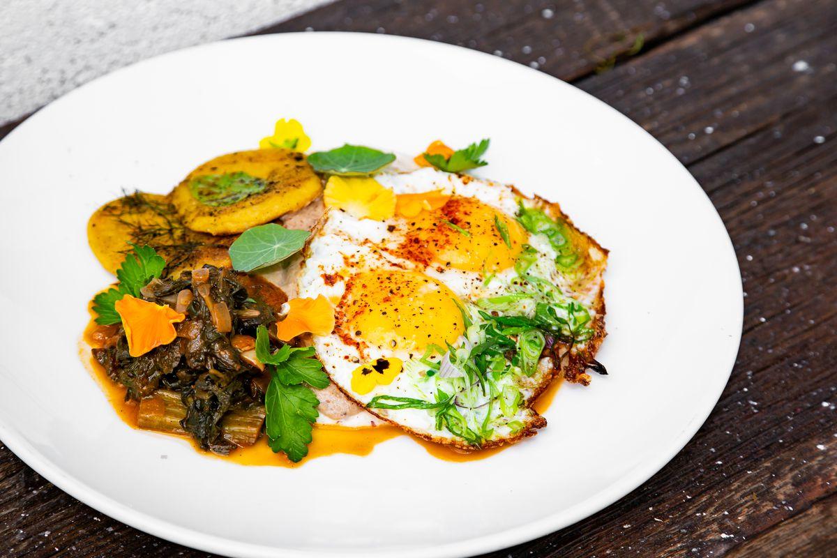 Huevos rancheros with red bolita grits, guisado greens, Sea Island peas, sope disks, and sunny side eggs