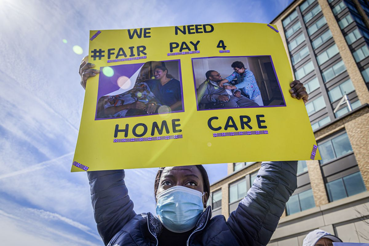 "A protester hold up a sign that reads, ""We need fair pay for home care."""