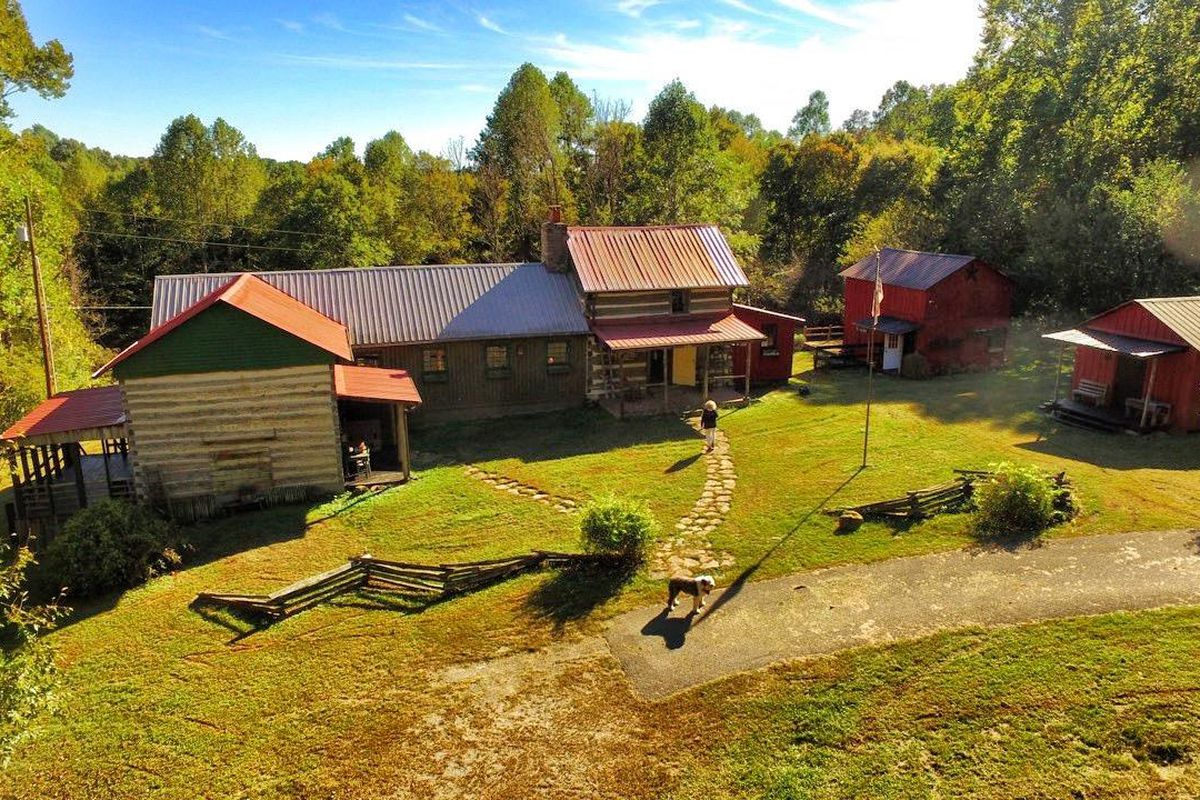 Farm compound with various outbuildings clad in red timber or made with logs.