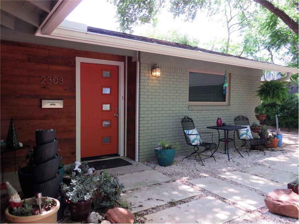 Front of 1961 house with green brick, wood, red door