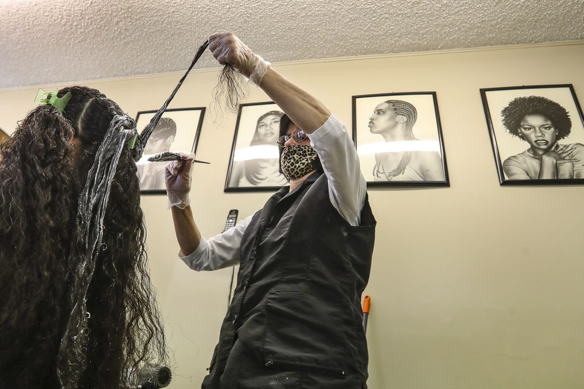 Trudy Chlepas, owner of Ebony & Ivory hair salon, brushes relaxer lotion onto a client's hair in the salon in South Salt Lake on Thursday, Feb. 11, 2021. The relaxer makes the hair easier to manage and straightens the curl.