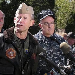 Rear Adm. Ted Branch, front left, and Adm. John Harvey, commander of U.S. Fleet Forces Command, speak with reporters Saturday, April 7, 2012, near the scene of a Navy jet crash in Virginia Beach, Va. The Navy and civilian authorities have just begun their investigation into the crash of the F/A-18D fighter that hit the complex on Friday.