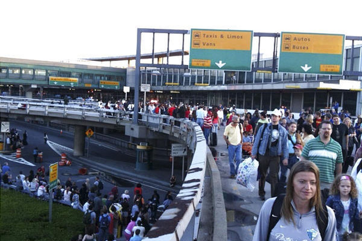 Travelers gather outside New York City's LaGuardia Airport during an evacuation Saturday morning.  Many travel plans were put on hold.