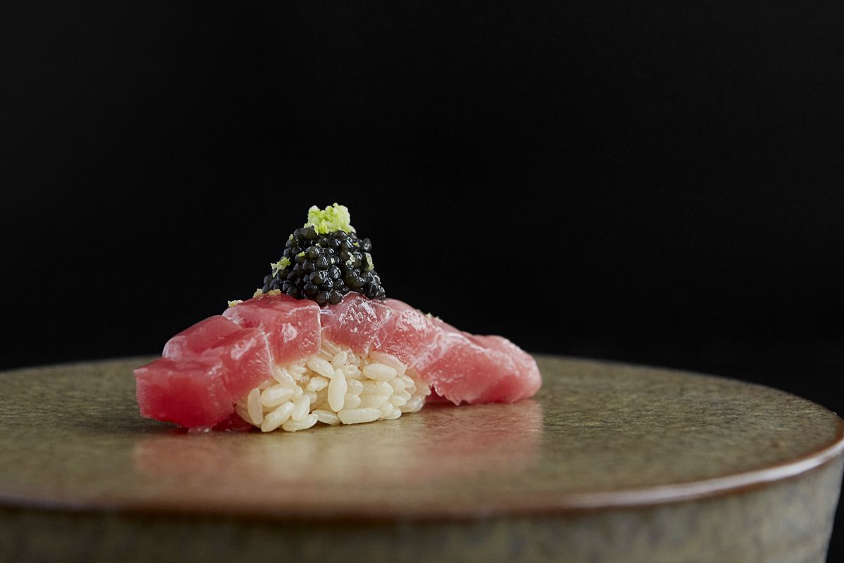 piece of tuna over rice topped with caviar on a plate with a black background