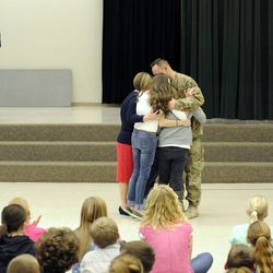 Air Force Tech Sgt. Edward Goettig embraces his wife, Tracie, and daughters Bailee, Sydney and Addie after his big surprise visit to Addie at Fox Hollow Elementary School in Lehi on Thursday, March 6, 2014. Goettig had been deployed to Afghanistan since Aug. 27, 2013.