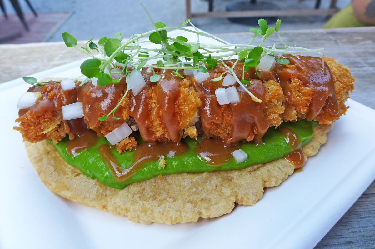 A half-moon of masa with a thick breaded steak on top drizzled with gravy and a green sauce between steak and masa.
