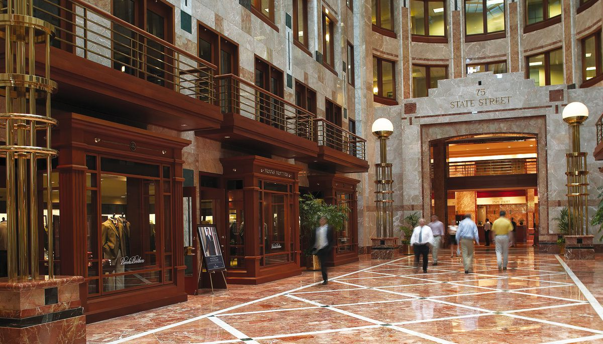 A building lobby with a long marble floor, high walls, and people walking about.
