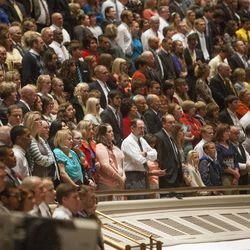 Audience members stand and sing during the Saturday morning session of the 183rd Semiannual General Conference for the Church of Jesus Christ of Latter-day Saints Saturday, Oct. 5, 2013 inside the Conference Center.
