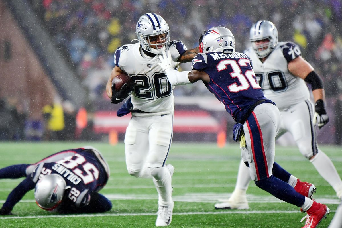 Tony Pollard of the Dallas Cowboys runs with the ball during the first half against Devin McCourty of the New England Patriots in the game at Gillette Stadium on November 24, 2019 in Foxborough, Massachusetts.