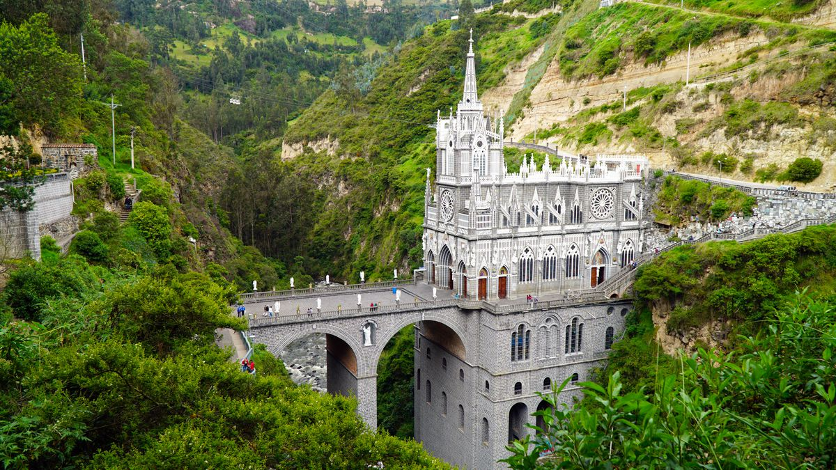 """The exterior of <span data-author=""""843"""">Las Lajas Sanctuary in Colombia. The church is connected to a canyon with a bridge. The facade of the church is grey with white spires. </span>"""
