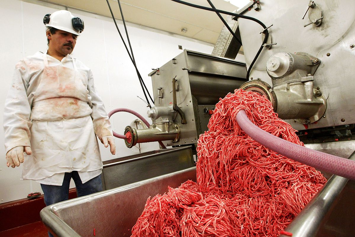 A worker monitors a meat grinding machine in 2003.