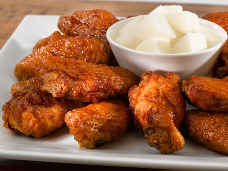 Fried chicken wings and drumsticks sit on a white plate, surrounding a small white bowl of white radish cubes