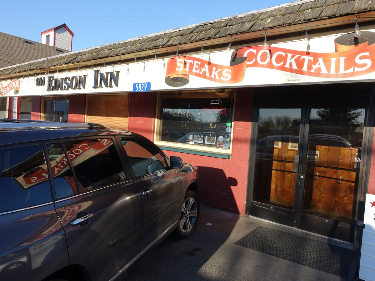 """The exterior of the Old Edison Inn, with an orange banner that says """"Steaks and Cocktails,"""" and a large van parked out front"""