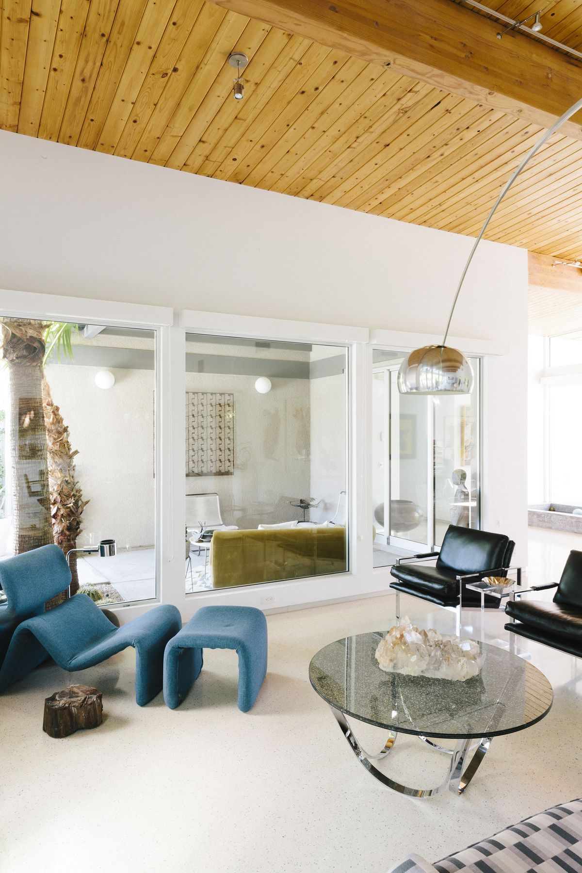 A living area. There is a bright blue lounge chair with a foot rest. There is a glass coffee table and two black chairs. A lamp hangs over the table. The ceiling is wooden. There are glass doors looking into another room