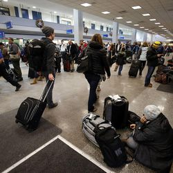 Travelers wait or line up at Salt Lake City International Airport as flights were delayed or canceled during a snowstorm, Thursday, Dec. 19, 2013.