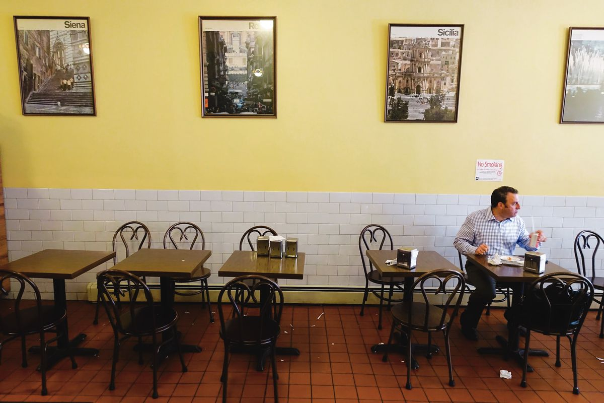 One man eats alone in Galleria Umberto. In the background, photographs line the pale yellow wall.