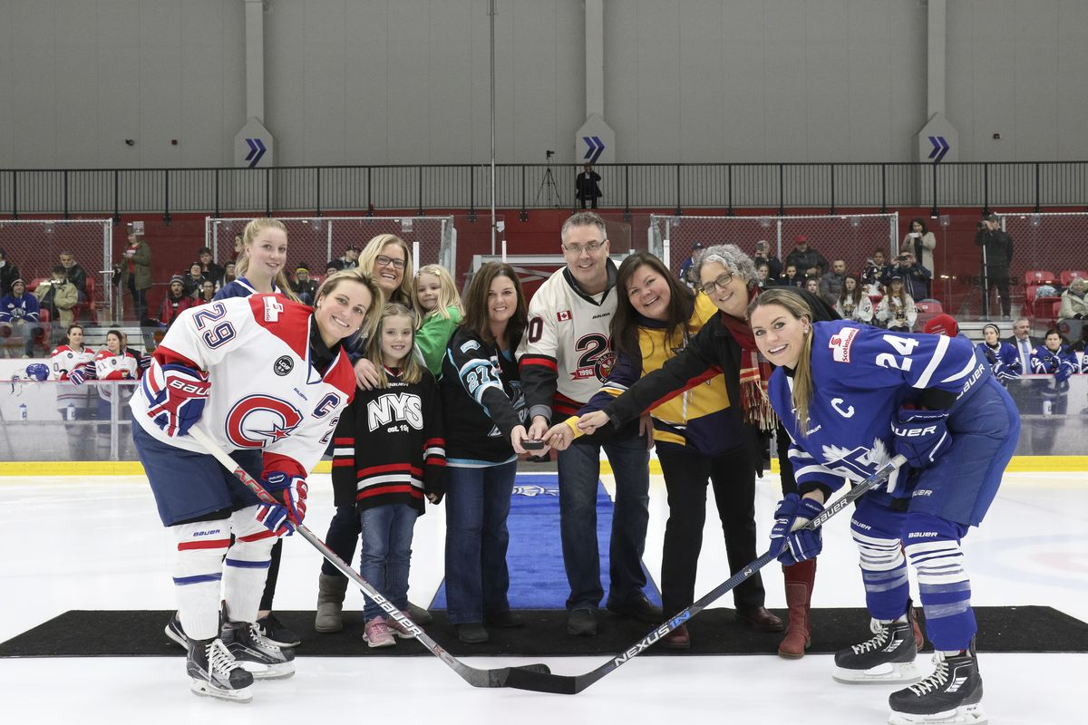 Marie-Philip Poulin and Natalie Spooner take the ceremonial faceoff with representatives from several Ontario girls hockey leagues.