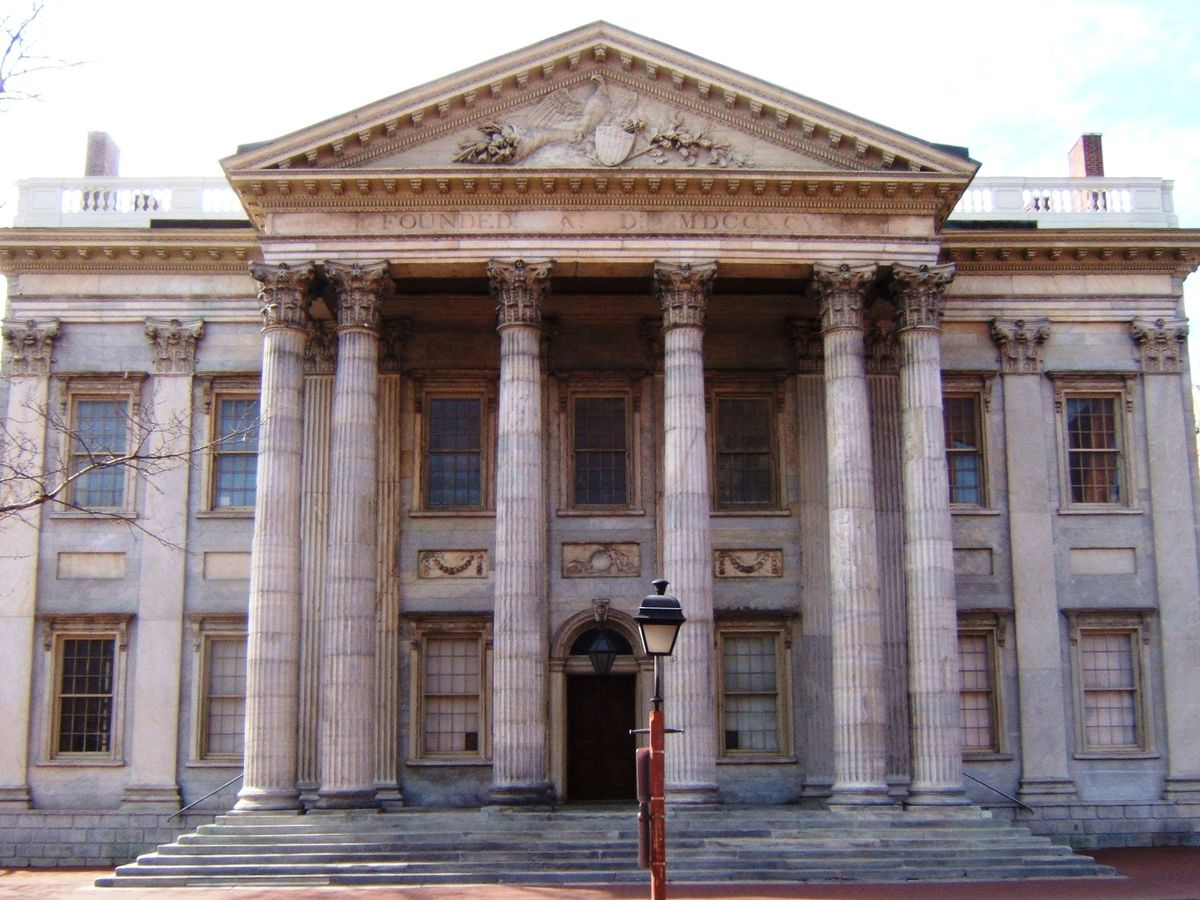 The exterior of the First Bank of the United States. The facade is grey with columns.
