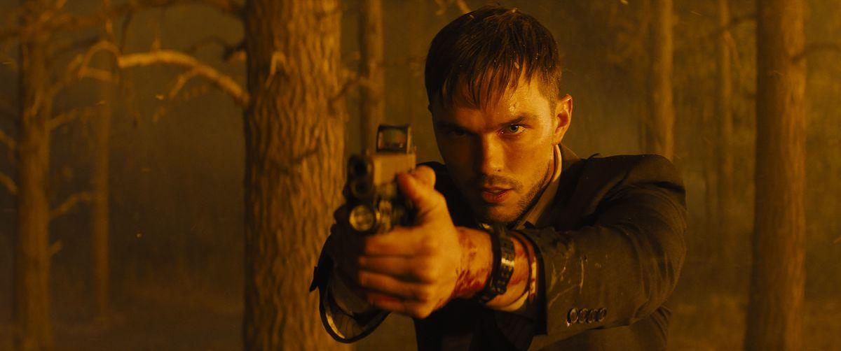 Un agitado y ensangrentado Nicholas Hoult apunta un arma fuera de la pantalla en Los que me desean muerto