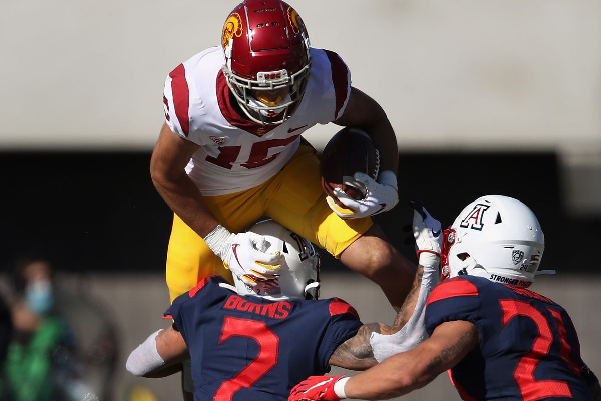 Wide receiver Drake London of the USC Trojans attempts to leap over defensive back Lorenzo Burns of the Arizona Wildcats after a reception during the first half of the PAC-12 football game at Arizona Stadium on November 14, 2020 in Tucson, Arizona. The Trojans defeated the Wildcats 34-30.