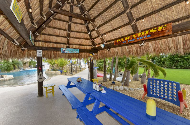 A bright blue picnic table sits under a tiki hut next to a pool.
