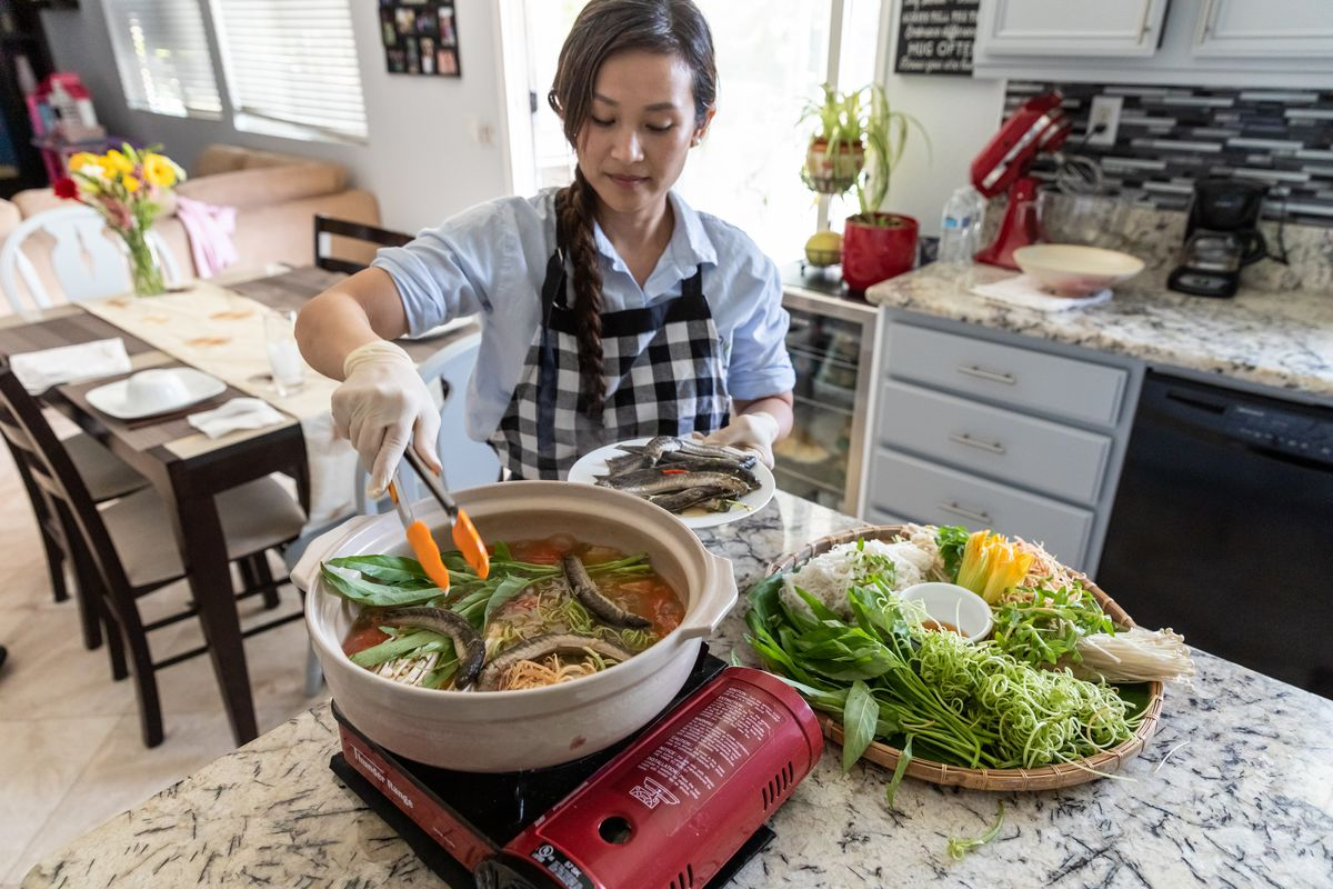 My Nhan Tran prepares a Vietnamese stew in her Foodnome-listed home restaurant My Fair Kitchen with a layout of colorful vegetables.