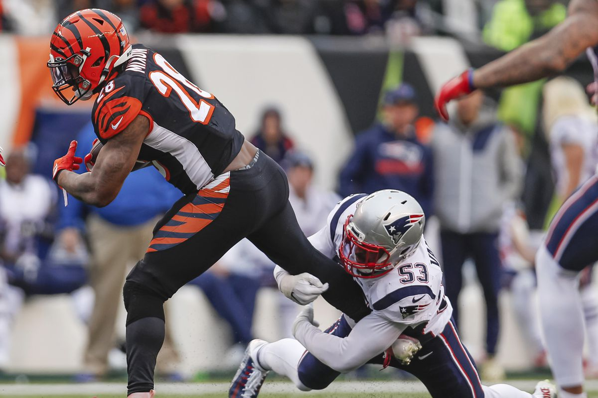 Joe Mixon of the Cincinnati Bengals runs the ball as Kyle Van Noy of the New England Patriots hangs on for the tackle during the second half at Paul Brown Stadium on December 15, 2019 in Cincinnati, Ohio.
