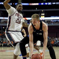 BYU forward Eric Mika, right, reacts as he drives against Illinois center Mike Thorne Jr during the second half of an NCAA college basketball game Saturday, Dec. 17, 2016, in Chicago. Illinois won 75-73. (AP Photo/Nam Y. Huh)