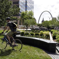 Jim Neumer rides through Citygarden, a sculpture garden in St. Louis. City leaders hope the garden will become one of the nation's great public places.
