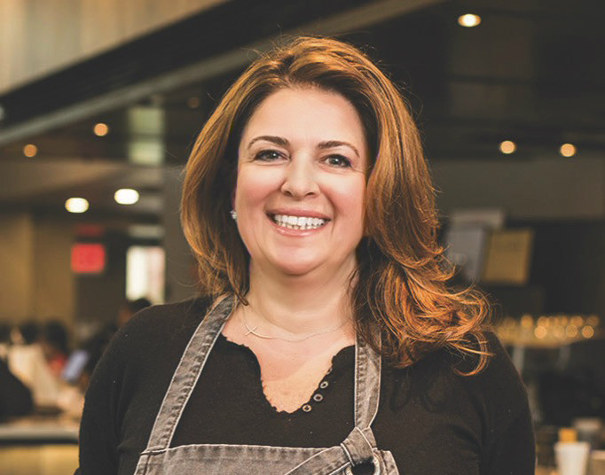 Closeup headshot of a smiling woman wearing a denim apron over a black top