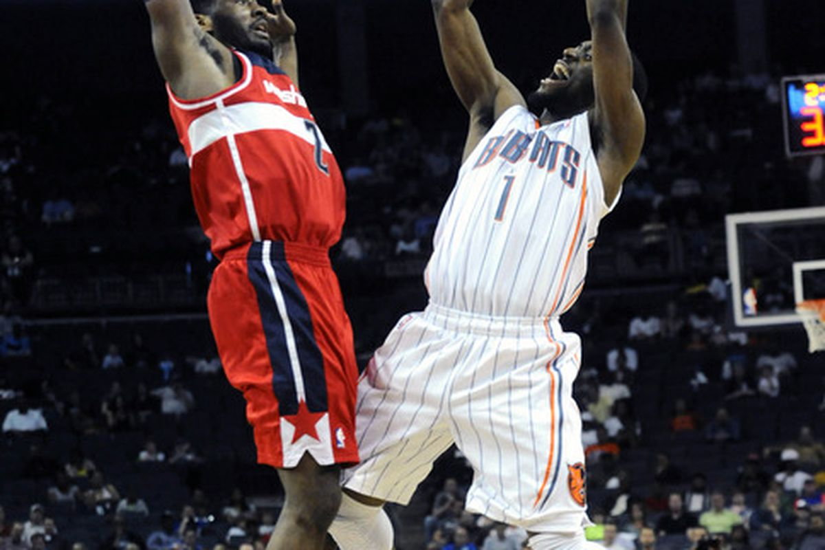 April 9, 2012; Charlotte, NC, USA; Charlotte Bobcats guard Kemba Walker (1) shoots as he is defended by Washington Wizards guard John Wall (2) during the game at Time Warner Cable Arena. Wizards win 113-85. Mandatory Credit: Sam Sharpe-US PRESSWIRE