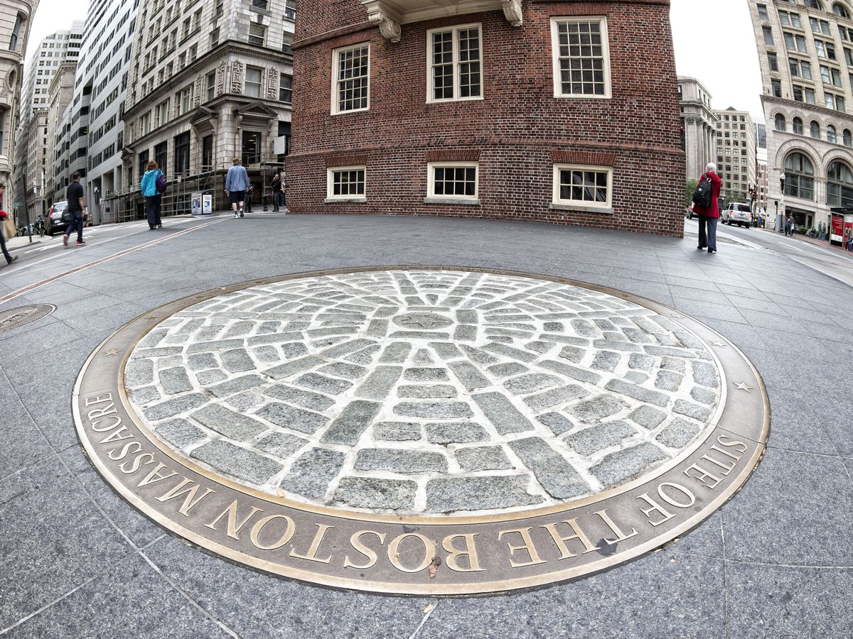 A round bronze marker built into the sidewalk of a city street.