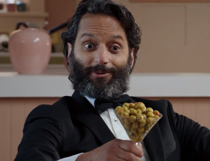 Jason Mantzoukas as Derek wearing a tuxedo and holding a martini glass full of green olives