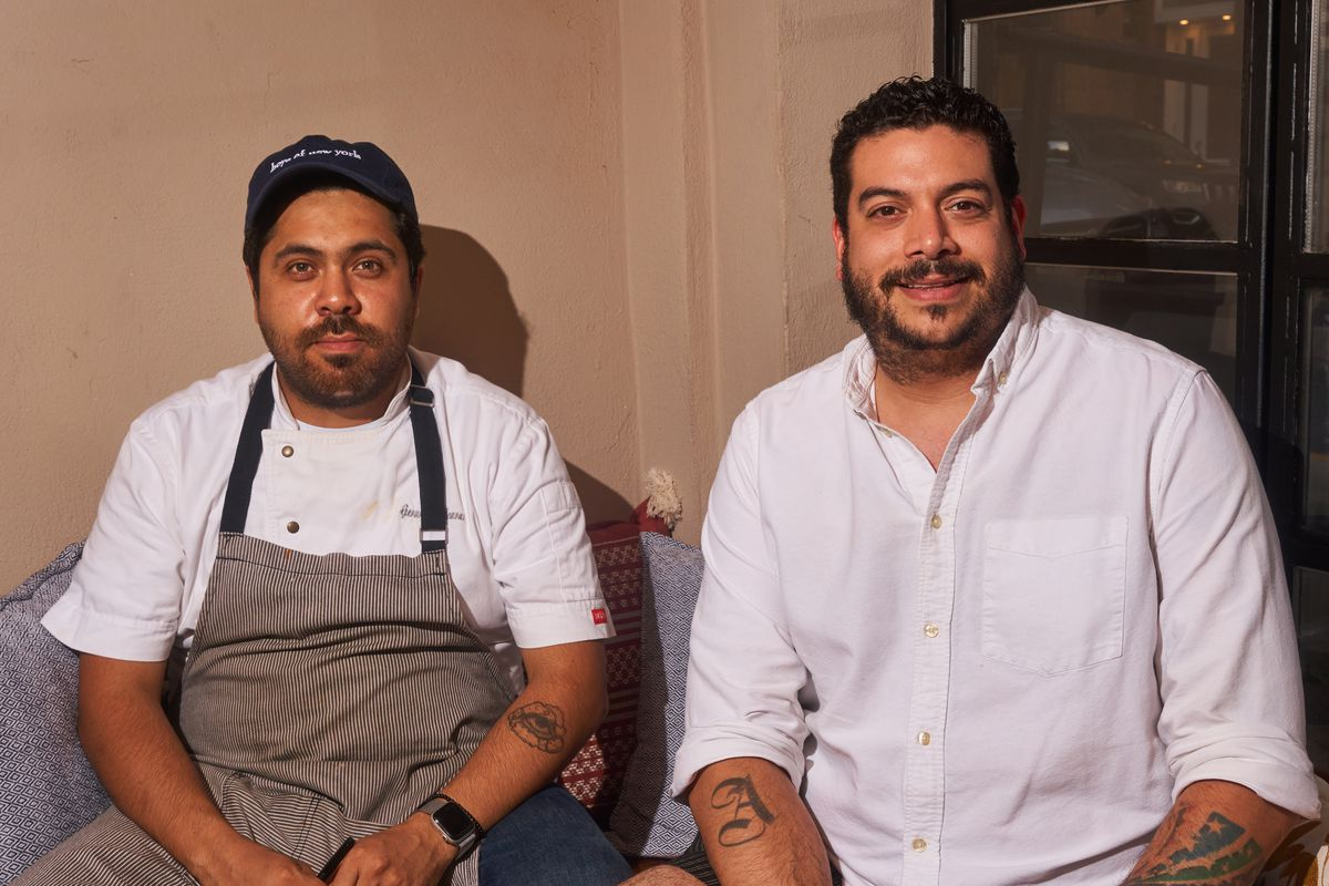 Two men, one in a white button-up shirt and another in a chef's apron and blue hat, smile for a photograph
