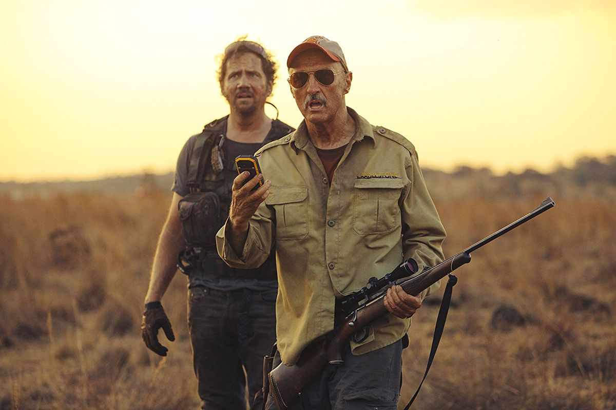 Tremors 5: Bloodline - Burt holding a scoped rifle and cellphone with Travis behind him
