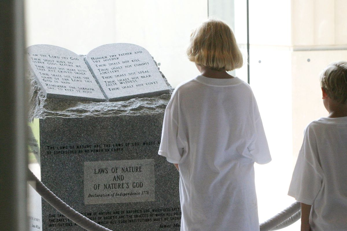 Children viewing a monument to the 10 Commandments that stood in the rotunda of Alabama's state judicial building until 2003