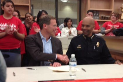 Superintendent Tom Boasberg and Denver Police Chief Robert White shake hands after signing a revised intergovernmental agreement Tuesday.
