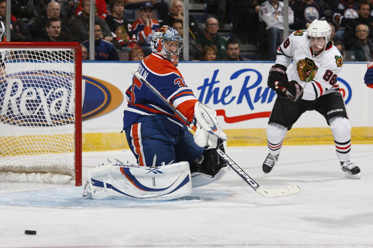 Nikolai Khabibulin of the Edmonton Oilers makes a sharp angle save off Patrick Kane of the Chicago Blackhawks in second-period action at Rexall Place November 17 2010 in Edmonton Alberta Canada. (Photo by Dale MacMillan/Getty Images)