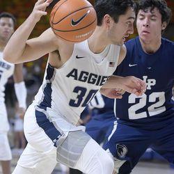 Utah State guard Abel Porter (30) drives to the basket as Life Pacific guard Dean Waltz (22) defends during an NCAA basketball game, Saturday, Dec. 16, 2017, in Logan, Utah. (Eli Lucero/Herald Journal via AP)