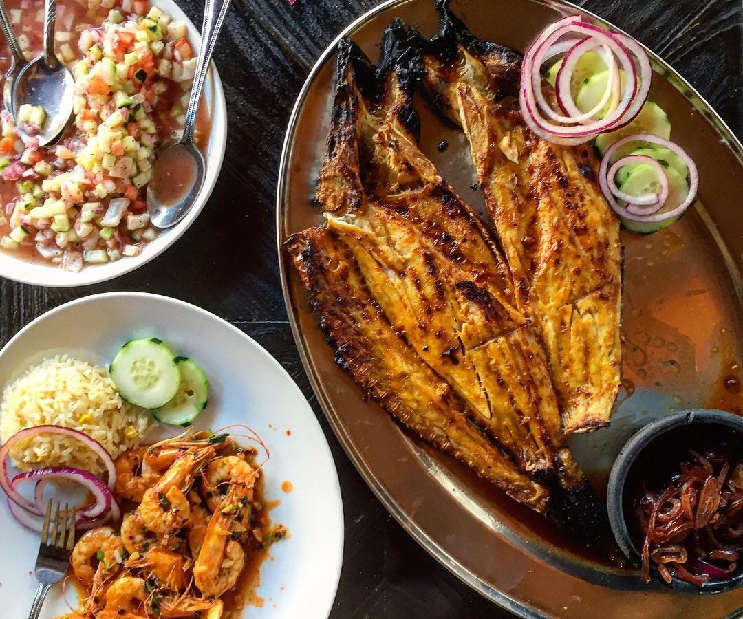 A top down view of grilled fish, shrimp, and ceviche.