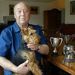 Poet Leslie Norris holds his Welch Terrier, Tansi, while he shows off some of the trophies he has won.