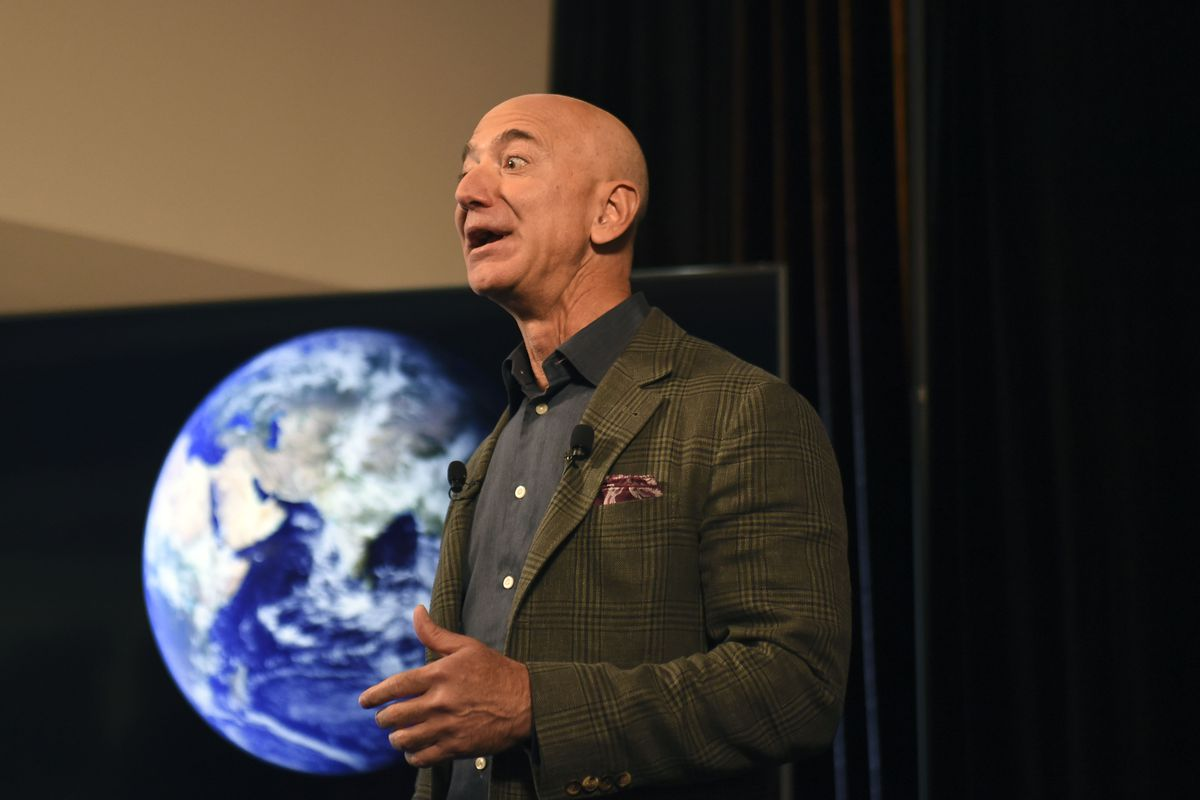Jeff Bezos in front of a photo of Earth.
